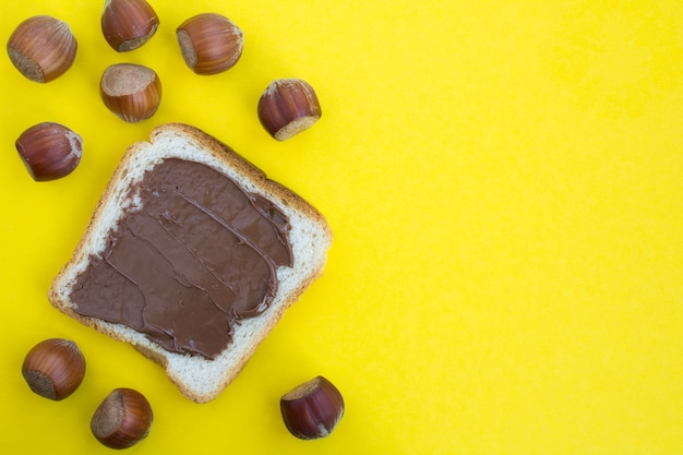 Top view of toast bread with chocolate cream on the yellow surface