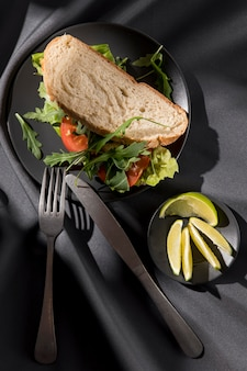 Top view of toast sandwich with tomatoes, greens and limes