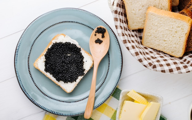 Top view toast with black caviar with a spoon on a plate with butter and bread in a basket