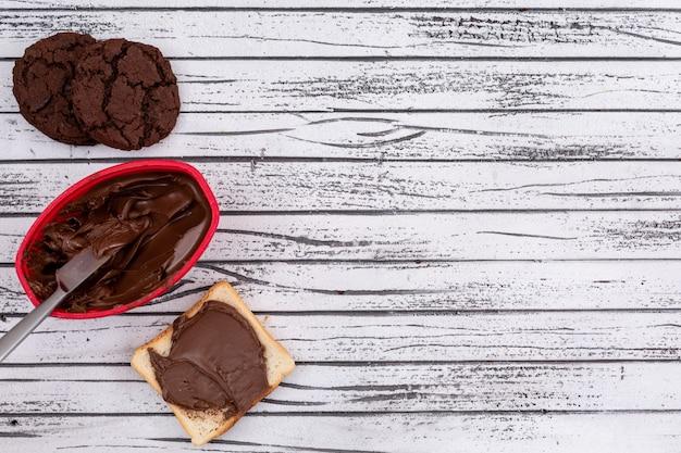 Vista superiore di pane tostato con cioccolato e biscotti e spazio della copia sull'orizzontale di legno bianco del fondo