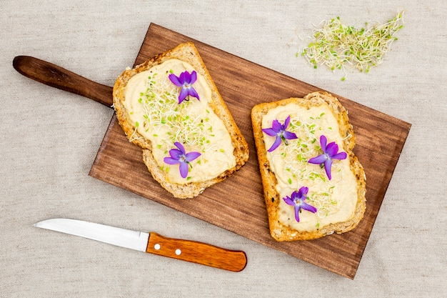 Top view of toast with flowers on chopping board