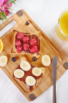 Top view on toast with peanut butter, raspberries and bananas