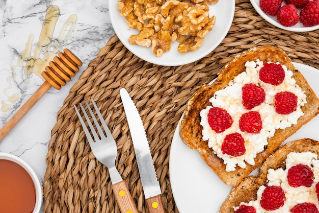 Top view of toast with raspberries and cutlery