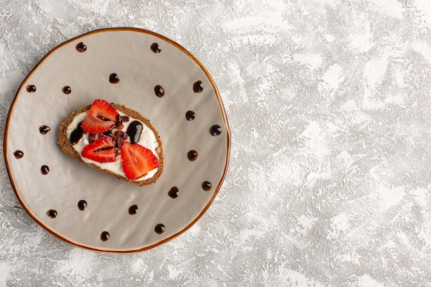 Top view of toast with strawberry and sour cream inside brown plate on the grey light surface