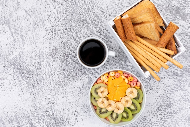 Top view of toasts and coffee with crackers, corn rings with copy space on white background horizontal
