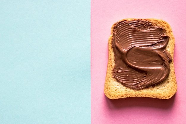 Top view of toasts with chocolate butter on white and pink background