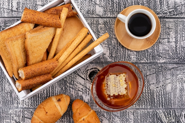 Top view of toasts with crackers in crate with honey and coffee on white surface horizontal