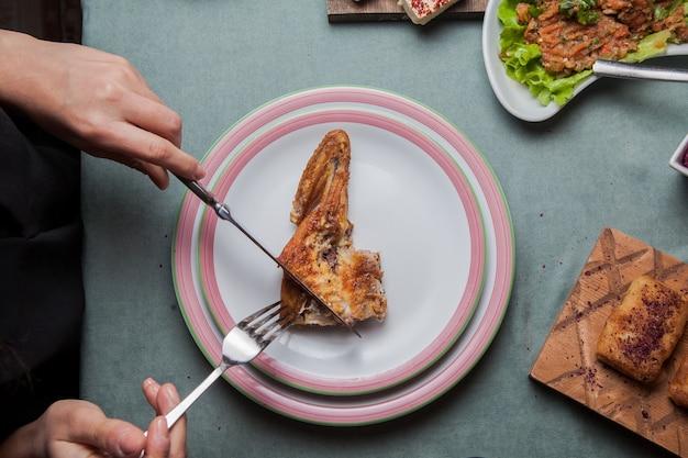 Pollo del tabacco di vista superiore in un piatto bianco su una tavola servita con un altro pasto, coltello, orizzontale della forcella