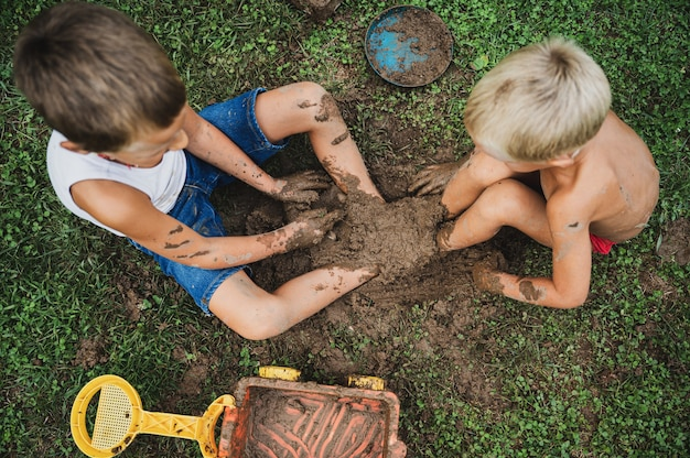 Top view of toddler brothers sitting in a grass having fun playing with mud burying their feet in it