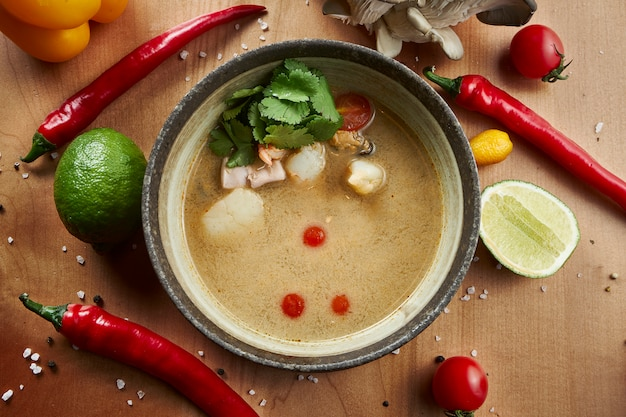 Top view tom yam with seafood in composition with ingredients. popular hot and sour thai soup. copy space. flat lay with spicy and tasty food. banner or menu photo. tom yum