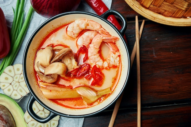 Top view tom yam with shrimp, seafood, coconut milk and chili pepper in composition with ingridients. popular hot and sour thai soup. copy space. tom yum