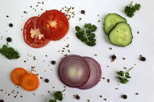 Вид сверху, ломтик помидора, огурца и моркови с листьями петрушки и луком лежат нарезанными кружками на белой поверхности