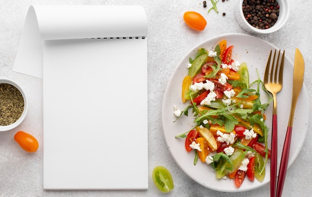 Top view tomato mix salad with feta cheese and blank notebook