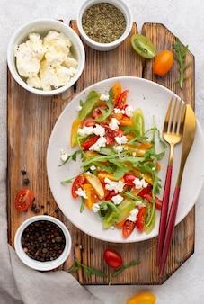 Салат-микс из помидоров с сыром фета, рукколой и черным перцем вид сверху