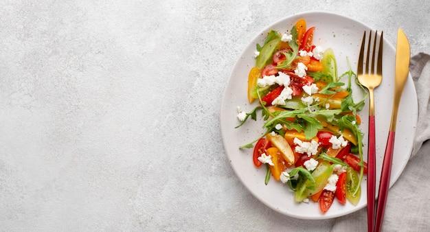 Вид сверху томатный салат с сыром фета и копией пространства
