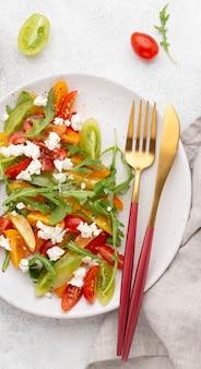 フェタチーズとカトラリーのトップビュートマトサラダ