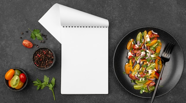 Top view tomato salad with feta cheese, rucola and blank notepad