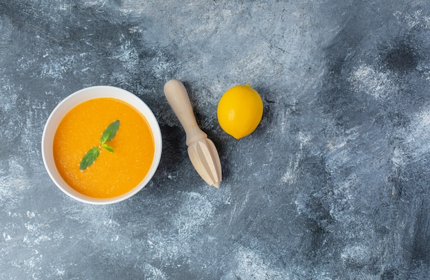 Top view of tomato soup and fresh lemon with lemon squeezer.