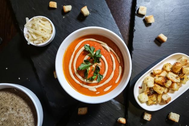 Zuppa di pomodoro vista dall'alto con formaggio e cracker su un supporto