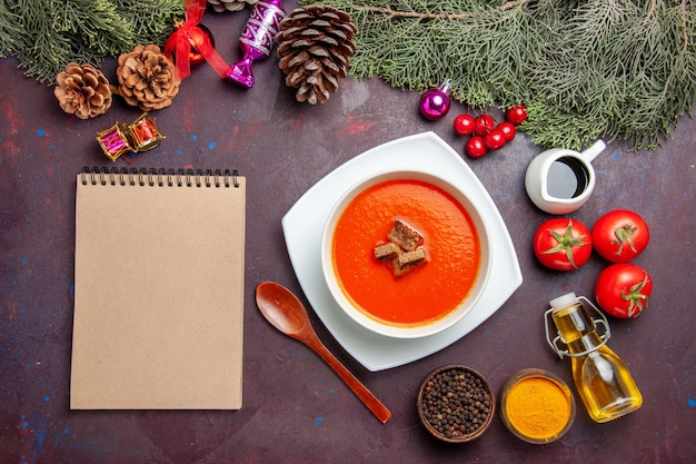 Top view of tomato soup with fresh tomatoes and seasonings on black