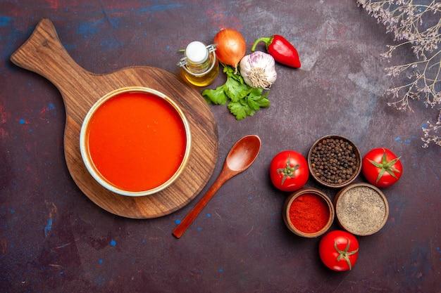 Vista dall'alto della zuppa di pomodoro con condimenti su viola nero