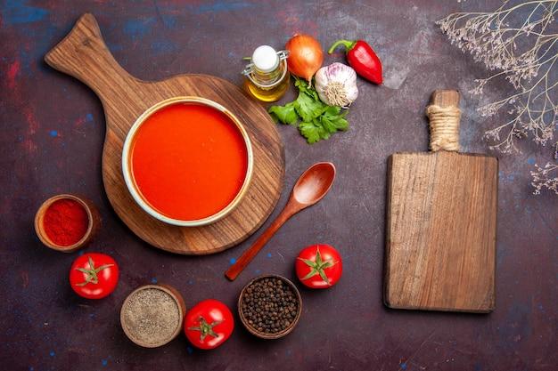 Vista dall'alto della zuppa di pomodoro con condimenti su nero