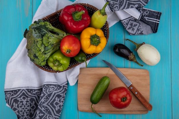 Vista dall'alto pomodoro con cetriolo sul tagliere con coltello e peperoni con broccoli in cestino e melanzane su sfondo turchese