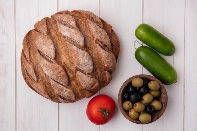 Вид сверху помидор с огурцами, буханка черного хлеба и оливки на белом фоне