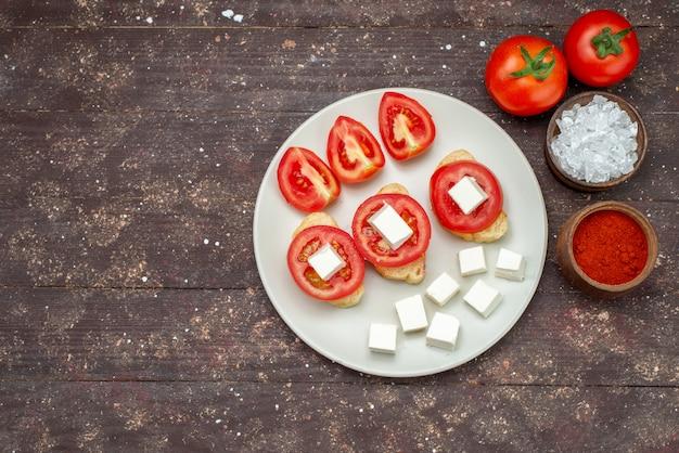 Вид сверху помидоры и сыр внутри белой тарелки с приправами на коричневом деревянном деревенском фоне еда овощной салат фото