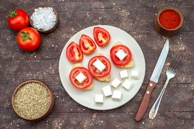 茶色の木製の素朴な背景食品野菜サラダに調味料と白い皿の中のトップビュートマトとチーズ