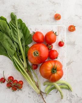 Вид сверху помидоры и листья салата