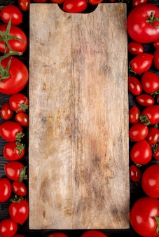 Top view of tomatoes around cutting board on wood