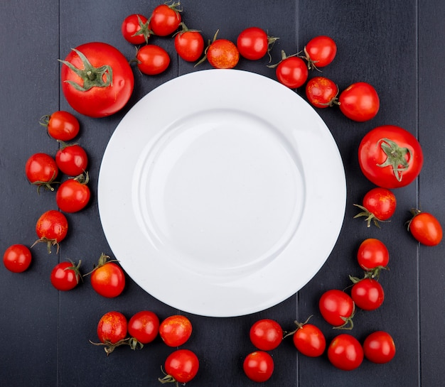 Top view of tomatoes around empty plate on black surface