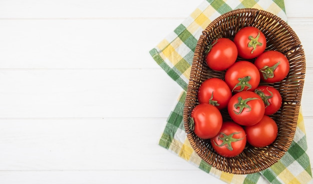 Top view of tomatoes in basket on cloth on right side and white surface with copy space