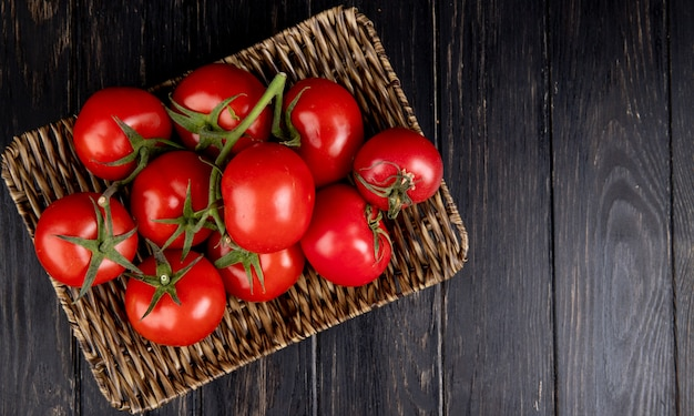 Top view of tomatoes in basket plate on wood with copy space