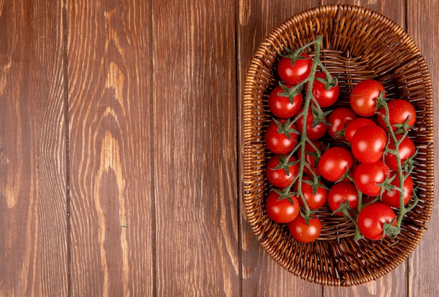 Top view of tomatoes in basket on right side and wood with copy space