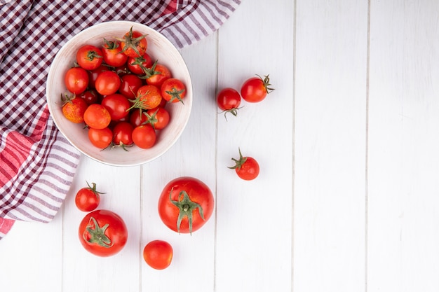 Top view of tomatoes in bowl on plaid cloth and on wooden surface