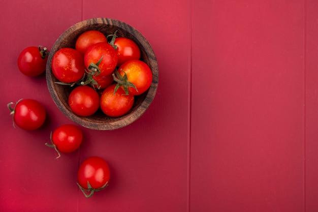 Vista dall'alto di pomodori in ciotola e sulla superficie rossa