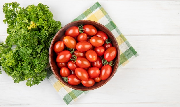 Top view of tomatoes in bowl with chinese coriander on cloth and wooden surface with copy space