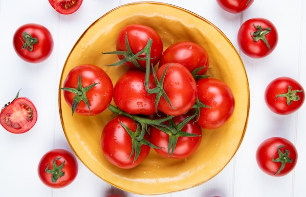 Top view of tomatoes in bowl with cut and whole ones on wooden surface