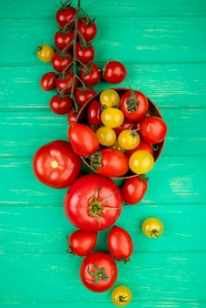 Top view of tomatoes in bowl with other ones on green surface