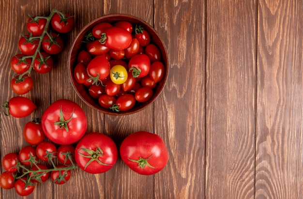 Top view of tomatoes in bowl with other ones on left side and wood with copy space