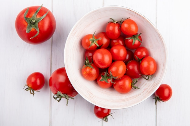 Top view of tomatoes in bowl and on wooden surface