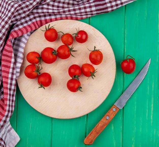 Vista dall'alto di pomodori sul tagliere con coltello e panno plaid sulla superficie verde