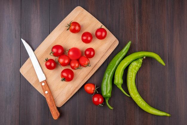 Vista superiore dei pomodori e del coltello sul tagliere con i peperoni su superficie di legno