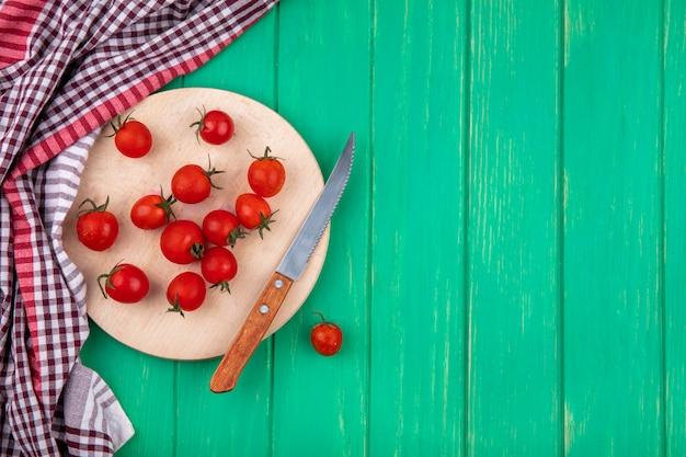 Vista dall'alto di pomodori e coltello sul tagliere con panno plaid sulla superficie verde