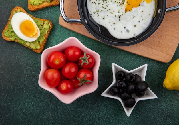 Top view of tomatoes on a pink bowl with black olives on a white bowl with fried egg in a frying pan on a wooden kitchen board on green surface
