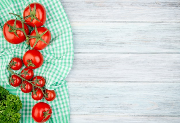 Top view of tomatoes on plaid cloth with coriander on wood with copy space