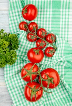 Top view of tomatoes on plaid cloth with coriander on wooden surface