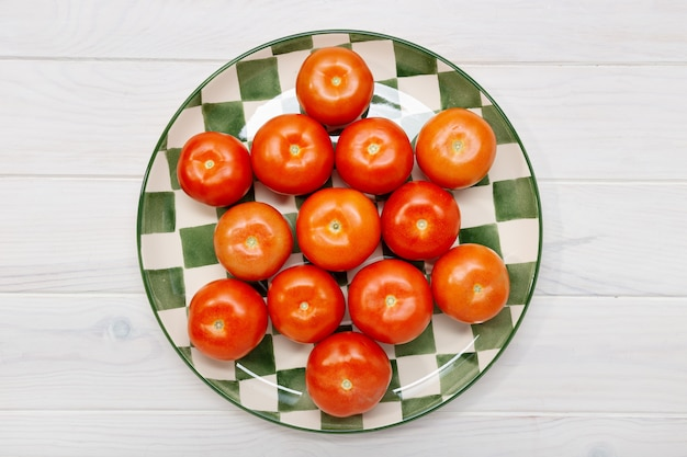 Top view of a tomatoes in plate on white wooden table